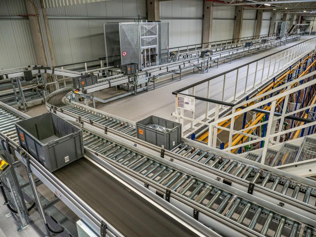Az automatikus alkatrészraktárat továbbítástechnikai megoldások kapcsolják össze az áruátvételi, komissiózási és csomagolási munkahelyekkel.